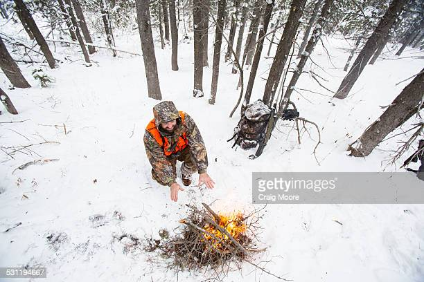 A male hunter stays warm next to a fire in the snow.