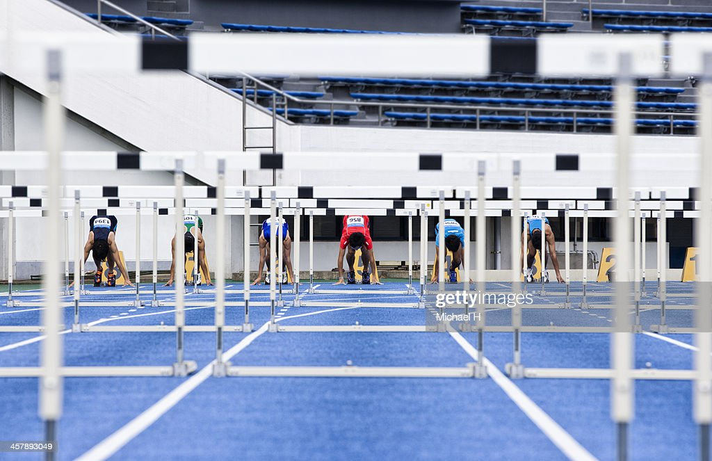 male hurdlers at starting line ストックフォト getty images