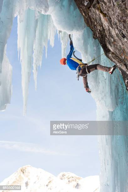 Male ice climber hanging on sharp icicle