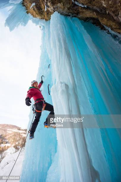 Male ice climber holding on a single ice axe