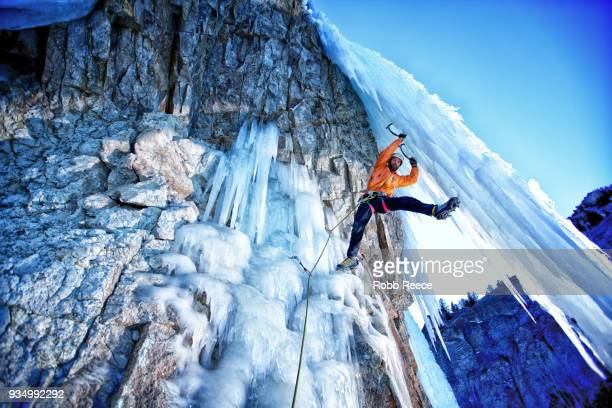 a male ice climber on a frozen waterfall - robb reece stock-fotos und bilder