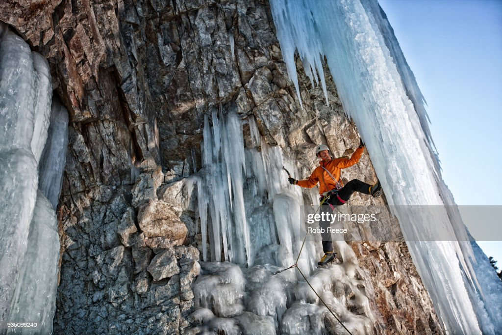 A male ice climber on a frozen waterfall : Stock Photo