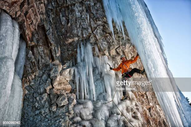 a male ice climber on a frozen waterfall - robb reece stockfoto's en -beelden