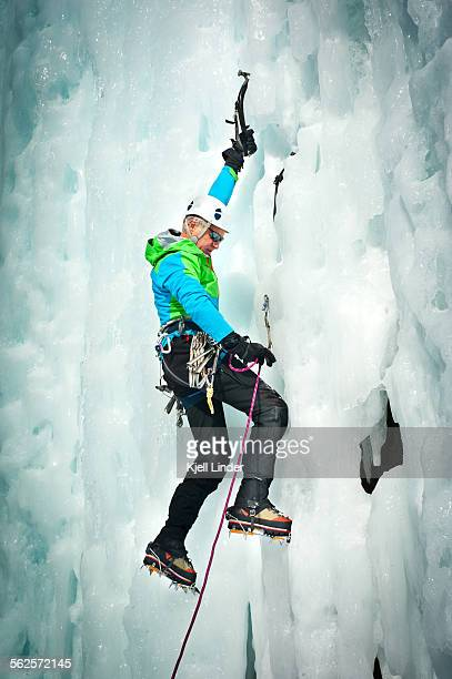 Male ice climber on frozen waterfall