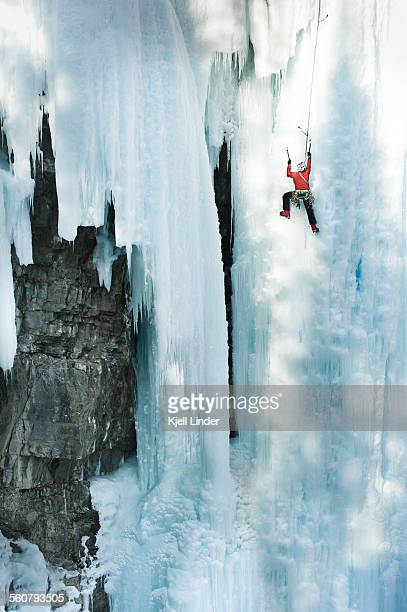 Male ice climber scales big ice-covered rock wall