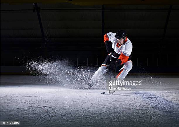 male ice hockey player taking puck - ice hockey stock pictures, royalty-free photos & images