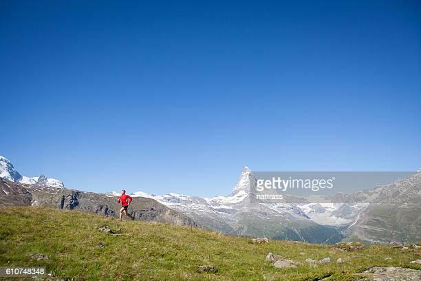 Male in red mountain running near the Matterhorn