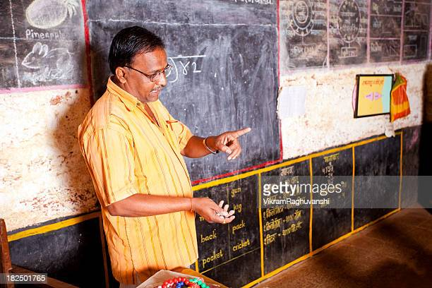 Male Indian teacher standing beside a blackboard