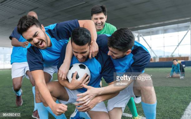 male indoor soccer players celebrating they just won the game and frustrated goal keeper sitting on the floor at the background - soccer team stock pictures, royalty-free photos & images