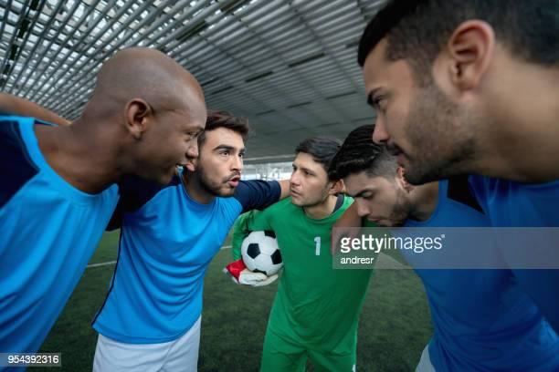 Équipe masculine de soccer intérieur sur un huddle parler avant de commencer le jeu