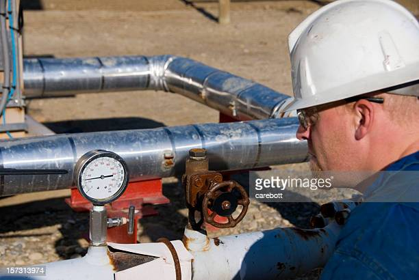 A male industrial worker and a set of pipes with a gauge