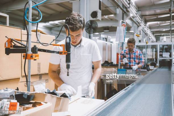 male industry employees work on production line at factory - production line stock pictures, royalty-free photos & images