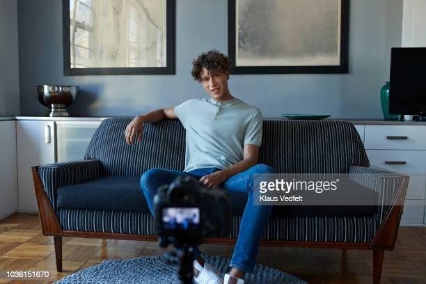 male influencer making video blog from his apartment - blue film video stock-fotos und bilder