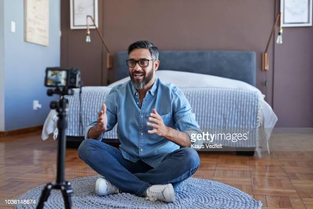 male influencer recording for video blog at home - blue film video stock-fotos und bilder