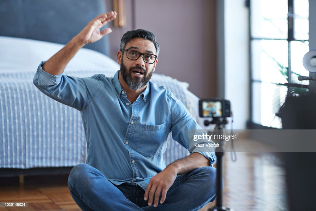 Male influencer recording for video blog from home : Stock Photo