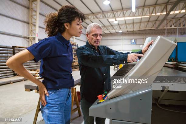 male instructor explaining apprentice in factory - izusek stock pictures, royalty-free photos & images