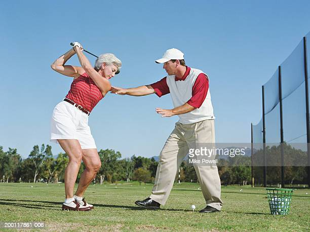 Male instructor helping mature woman with golf swing