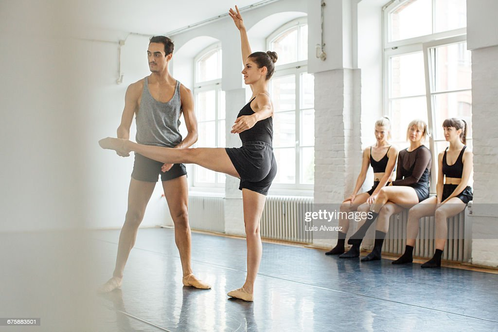 Male instructor teaching ballerina at studio : Stock Photo