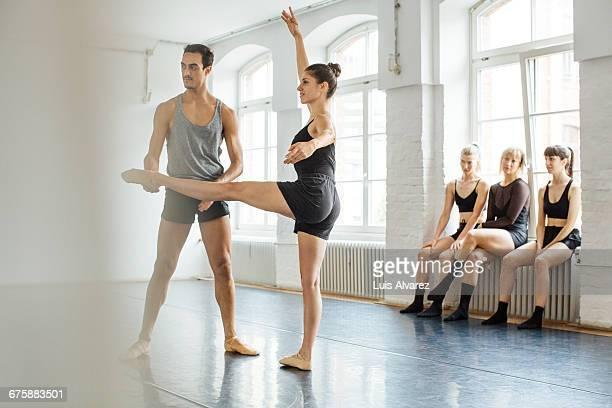 male instructor teaching ballerina at studio - ballettstudio stock-fotos und bilder