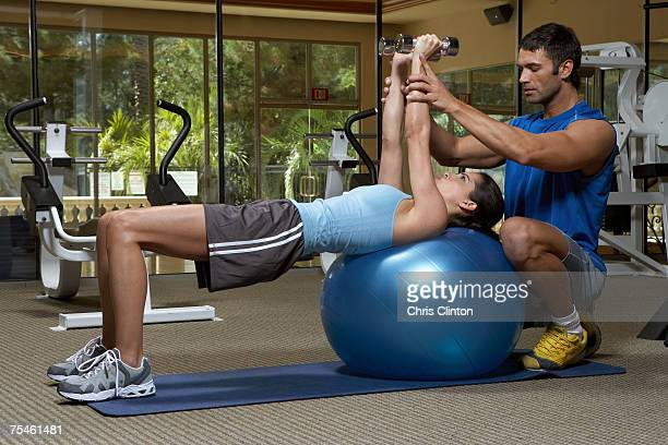 Male instructor training woman with dumbbells