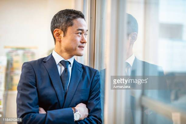 窓に立っている男性日本人病院管理者 - マネージャー ストックフォトと画像
