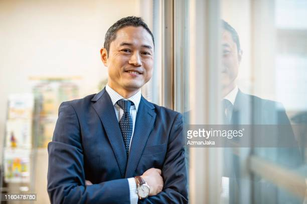 male japanese hospital administrator standing at window - administrator stock pictures, royalty-free photos & images