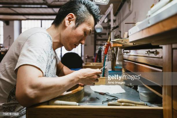 male jeweller inspecting metal at workbench - jewellery products stock photos and pictures