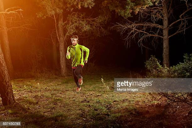 Male jogger running in forest at night