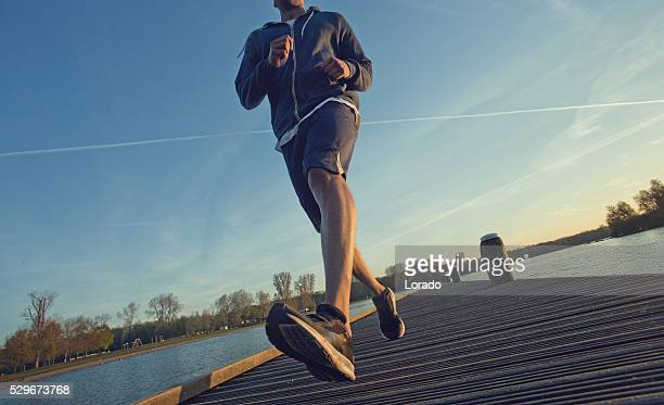 Male jogging at dawn on a lakeside pier