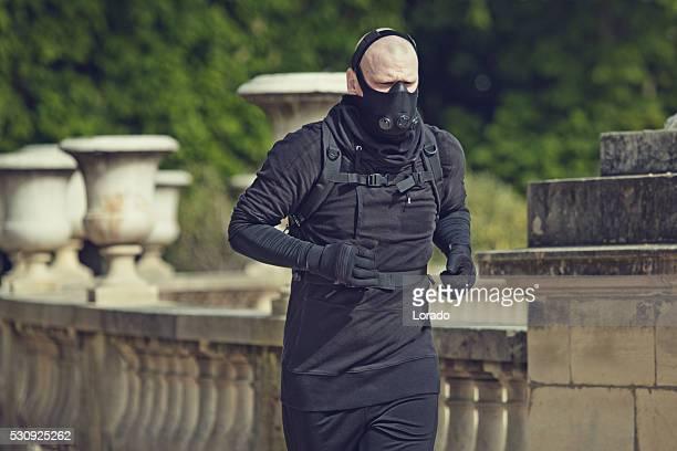 Male jogging in black in Paris park wearing breathing apparatus
