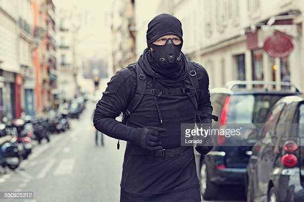 Male jogging in black in Paris street wearing breathing apparatus