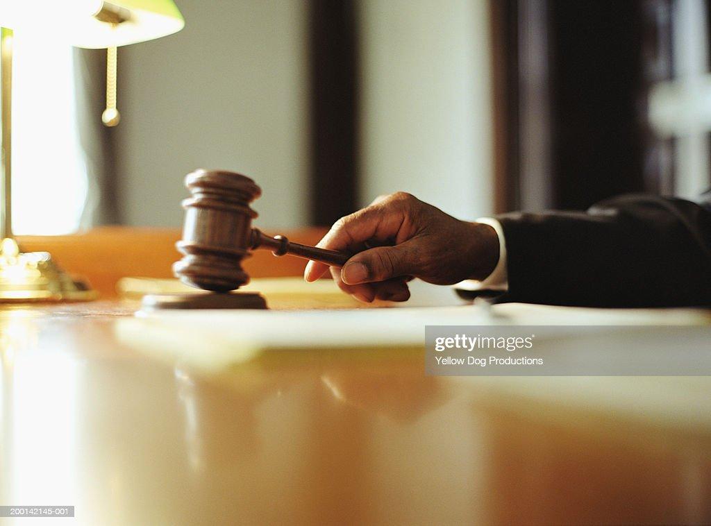 Male judge striking gavel in courtroom, close-up : Foto de stock