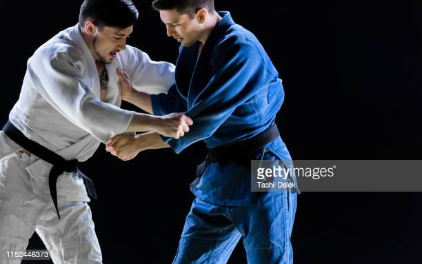 male judo players competing during match - judo stock pictures, royalty-free photos & images