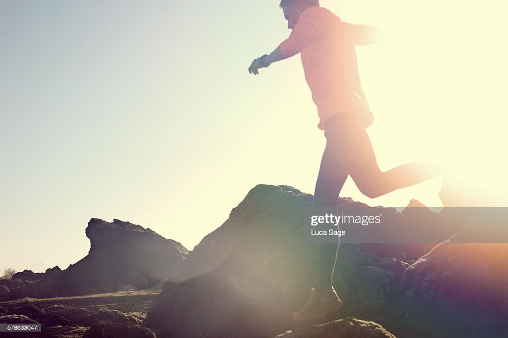 Male jumping and leaping over rocks in amazing sun : Stock Photo