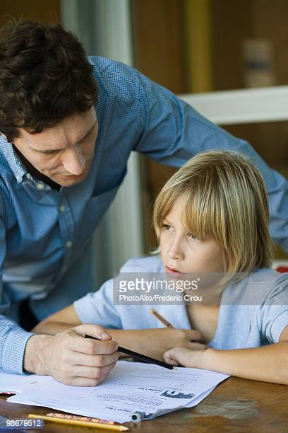 male junior high student listening as teacher explains difficult assignment - teacher bending over stock photos and pictures
