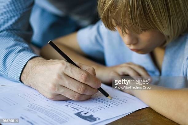 male junior high student watches as teacher corrects assignment, close-up - teacher bending over stock photos and pictures