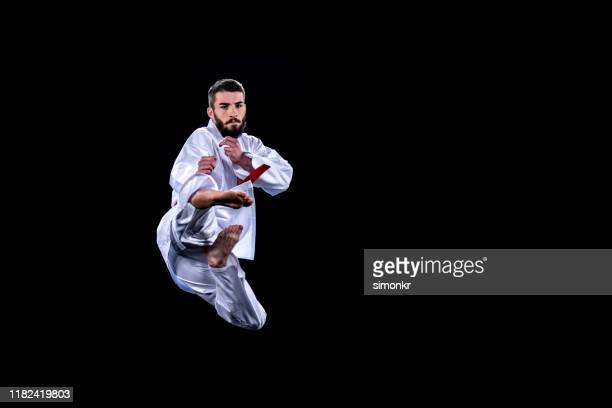 male karate player jumping in air for kick - martial arts stock pictures, royalty-free photos & images