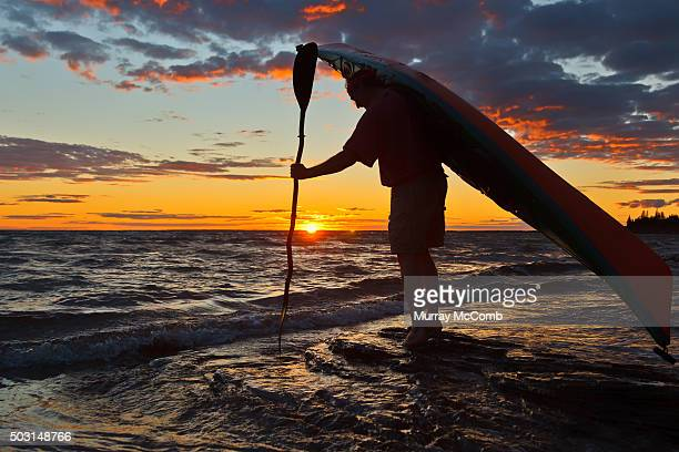 male kayaker heading out for sunset paddle - murray mccomb stock pictures, royalty-free photos & images