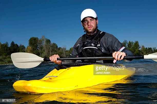 A male kayaker in a yellow playboat looks into the camera on the Clark Fork River, Missoula, Montana