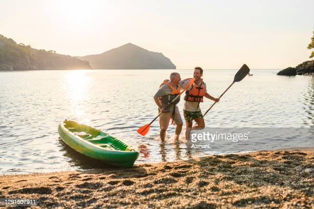 male kayakers walking onto beach with paddles after exercise - sea kayaking stock pictures, royalty-free photos & images