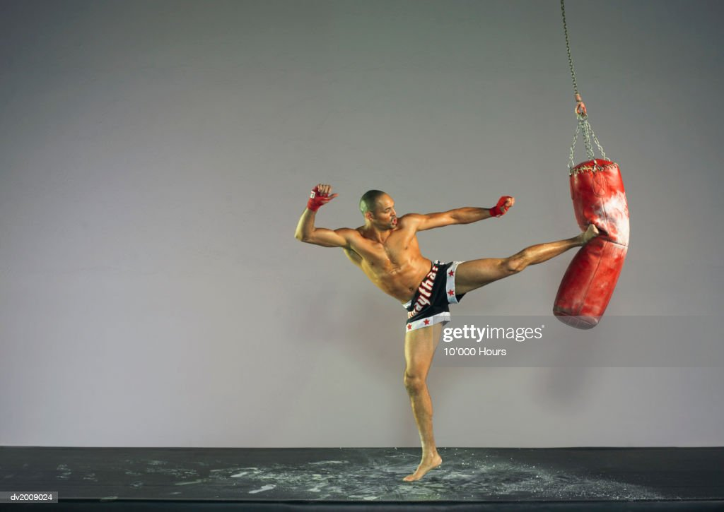 Male Kick Boxer Kicking a Punch Bag : Stock Photo