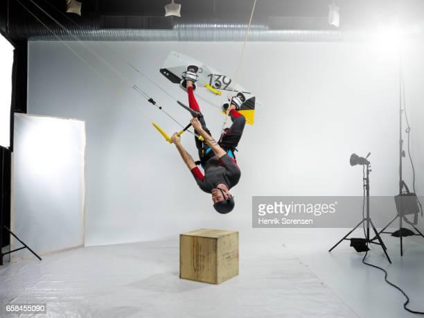 Male kitesurfer inverted in a studio