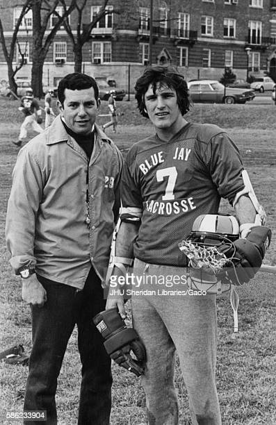 Male lacrosse player for Johns Hopkins University wearing a number 7 jersey and holding his gear standing on the field next to head coach Henry...