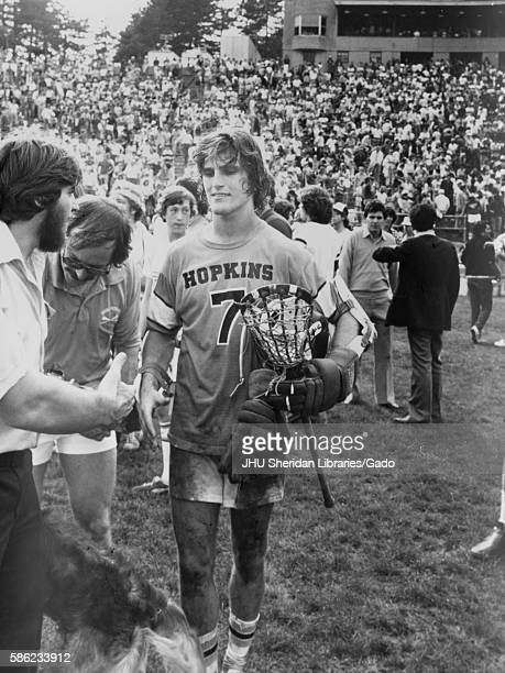 Male lacrosse player for Johns Hopkins University wearing number 7 uniform and holding gear preparing to shake the hand of a team assistant after the...