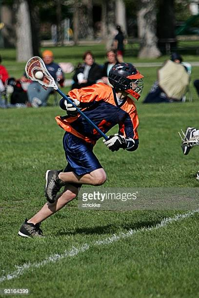 male lacrosse player in blue orange springs to action attack - face off sports play stock photos and pictures