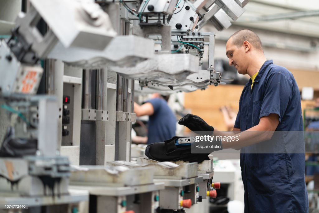 Male latin american worker at a shoe factory working on line production of boots : Stock Photo