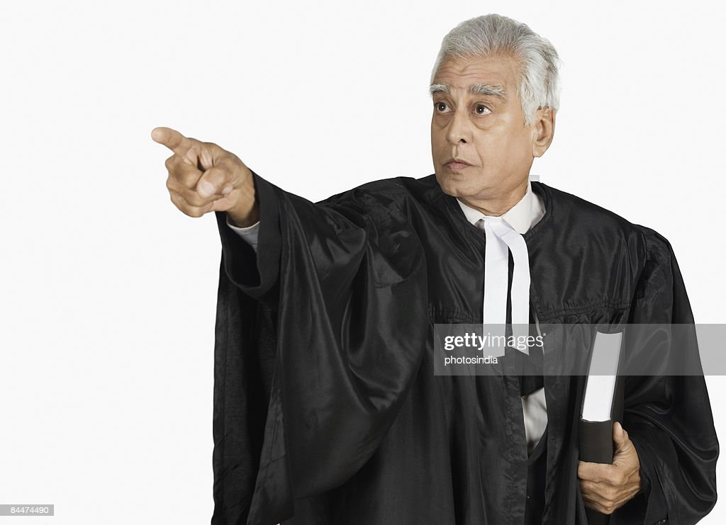 Male lawyer holding a book and pointing : Stock Photo
