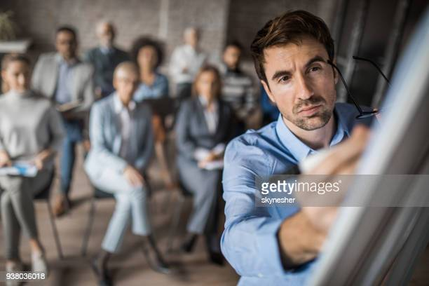 Male leader writing a business plan on whiteboard in a board room.