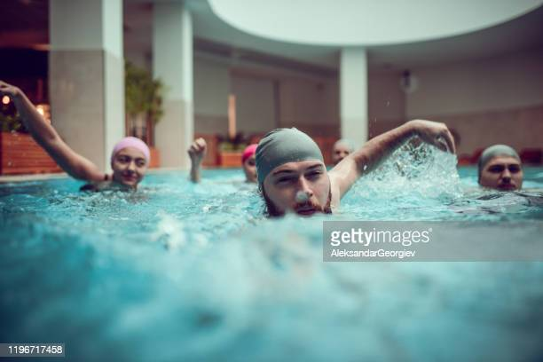 male leading in a swimming competition with him and friends - competition group stock pictures, royalty-free photos & images