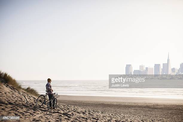 Male leaning on bike at beach looking @city scape